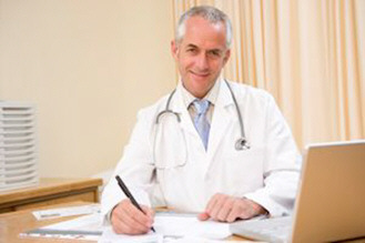 doctor-with-laptop-writing-in-doctors-office-xs