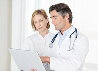 male doctor assisting his colleague while working on a laptop xs