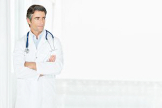 male doctor with arms folded looking at copy space xs