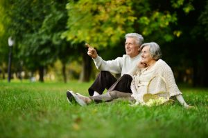 Elderly couple by the tree in the park 300x200