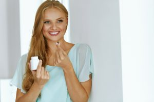 Smiling Woman holding pill 300x200