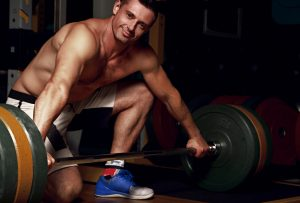 handsome smiling man lifting a barbell 300x203
