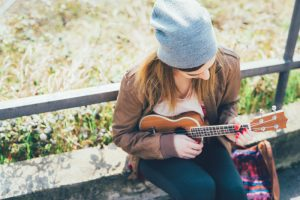 graphicstock young woman in the city playing ukulele busker musician composer concept_ SBI 304213511 1 300x200