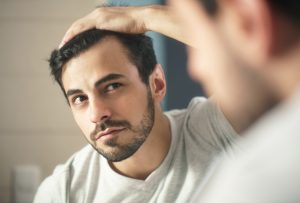 storyblocks latino person with beard grooming in bathroom at home white metrosexual man worried for hair loss and looking at mirror his receding hairline_H8mcRKLWQ 300x203