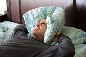 a man having trouble sleeping squeezes a pillow around his ears for some peace and quiet_Ht0bpVdASo 300x200