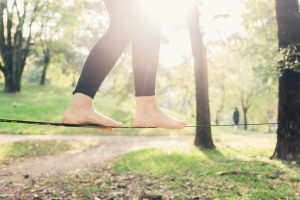 graphicstock close up on feet walking on tightrope or slackline outdoor in a city park in back light slacklining balance training concept_S6lDgAiKJZ 300x200
