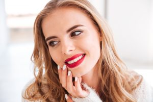 graphicstock close up portrait of a smiling attractive woman with red lipstick indoors SBI 302779574 300x200